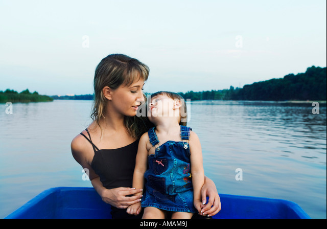 A mother and daughter sitting together in a boat - Stock Image