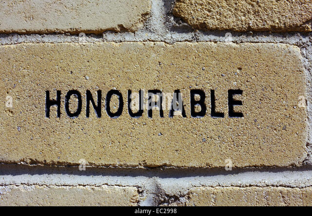 A brick with the word 'Honourable' carved into it. - Stock Image
