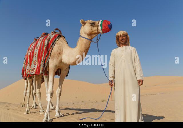Portrait of bedouin with camel in desert, Dubai, United Arab Emirates - Stock Image