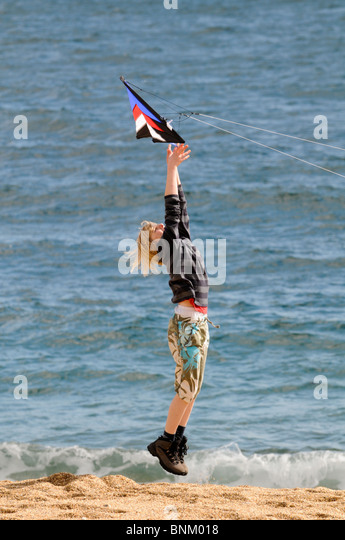 Young boy jumps up and is airborne as he lets go of a kite on a beach with waves at his feet - Stock-Bilder