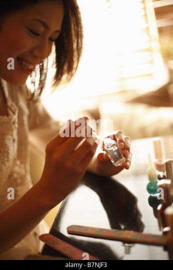 A woman painting her nails - Stock Image