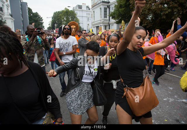 Dancing behind one of the parade sound systems. Notting Hill Carnival in West London. A celebration of West Indian - Stock Image