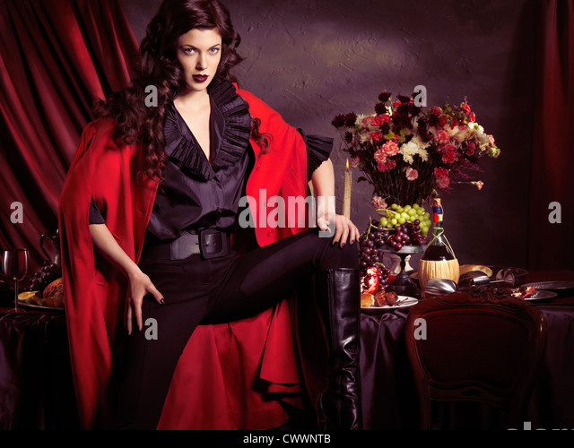 Beautiful fashionably dressed young woman wearing black with red coat posing in front of festive table filled with - Stock Image