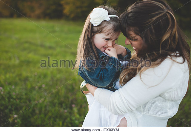 Mother holding young daughter, outdoors - Stock Image
