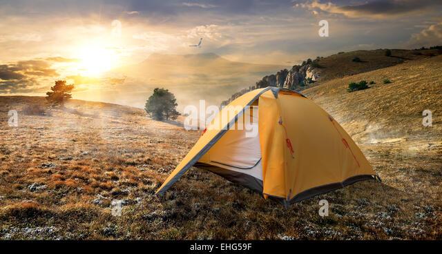 Tourist tent in autumn mountains at sunrise - Stock-Bilder