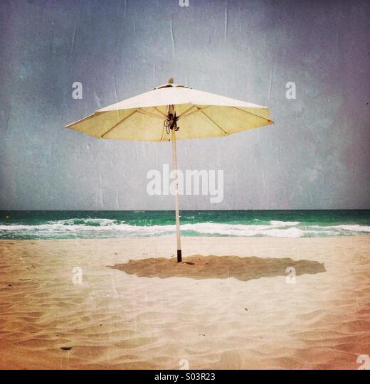 A single umbrella on the beach. Abu Dhabi, U.A.E. - Stock Image