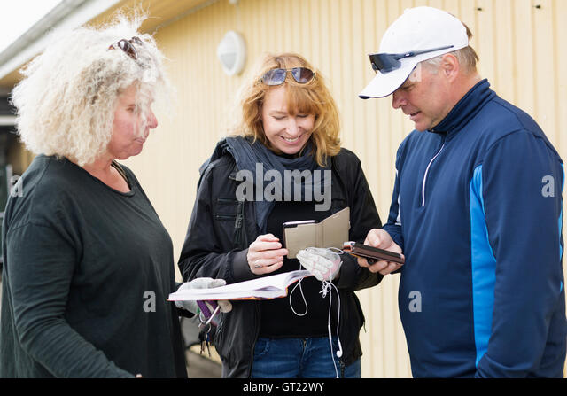 Happy friends holding mobile phones and diary at golf course - Stock-Bilder