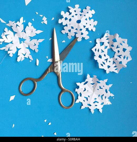 Scissors and paper snowflakes - Stock Image