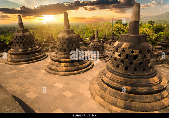 Sunset with the buddhist stupas at Borobudur temple, Indonesia - Stock Image