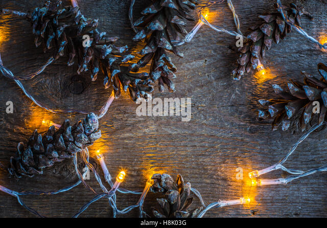 Christmas lights and pine cones on wooden rustic background. - Stock Image