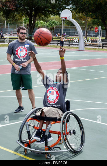 Florida FL Miami Tropical Park Paralympic Experience sports volunteer helping disabled basketball court wheelchair - Stock Image