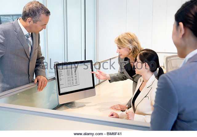 Businesswoman reviewing co-worker's work on monitor - Stock Image