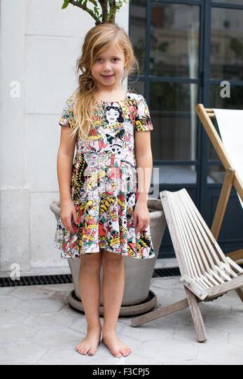 Little girl standing outdoors, portrait - Stock Image
