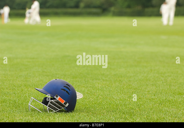 Cricket helmet on a cricket ground - Stock Image