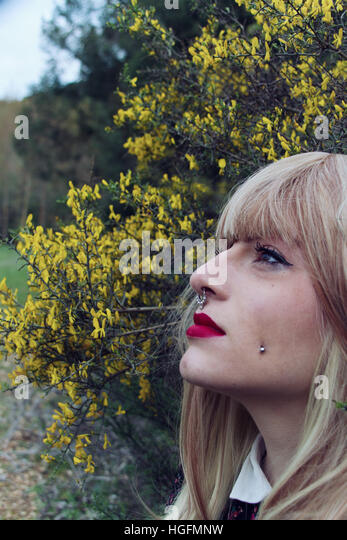 Young woman look into space with a lot of yellow flowers as background - Stock Image