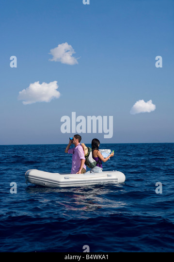 Couple lost at sea on little boat - Stock Image