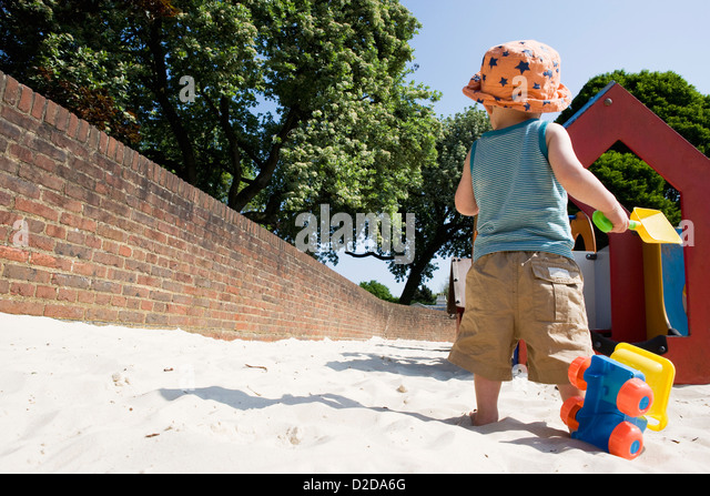 A young boy contemplating his choices at a playground - Stock Image