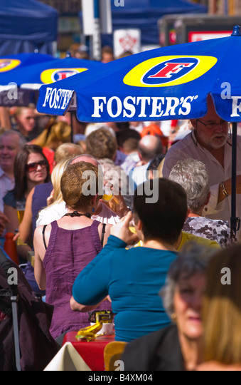 People sat drinking under FOSTERS umbrellas at Abergavenny Food Festival - Stock Image