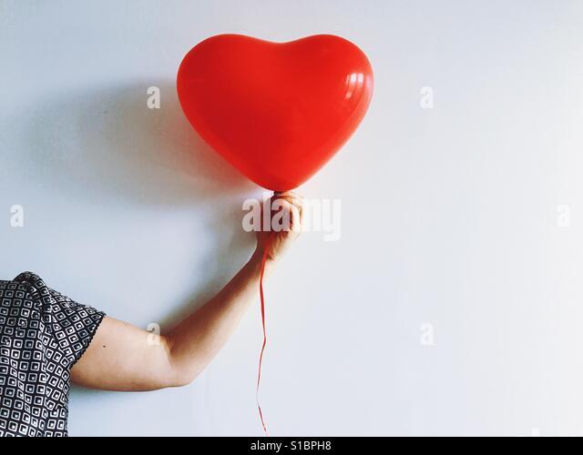 Woman holding heart shaped balloon - Stock Image