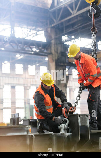 Steel workers fastening crane chain to steel in factory - Stock Image