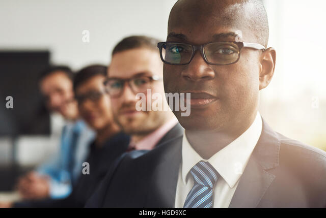Handsome black business man with three employees and back to large bright office window with light flare - Stock Image