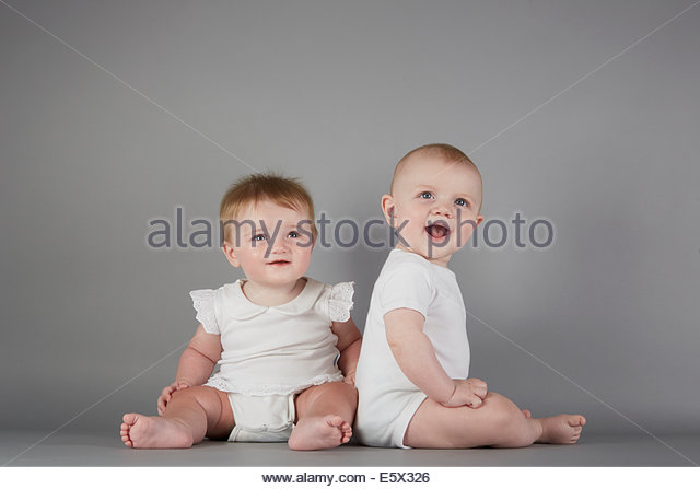 Studio portrait of smiling baby boy and baby girl - Stock Image