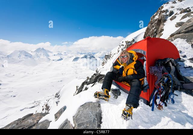 A happy mountaineer sitting in the doorway of her tent - Stock-Bilder