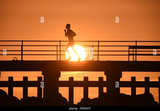 Aberystwyth, Wales, UK. 17th August, 2015. UK Weather: A lone man jogs in silhouette at sunset along the harbour - Stock-Bilder