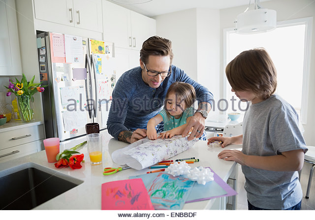 Father and children wrapping Mothers Day gift kitchen - Stock Image