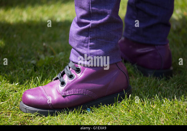 A pair of purple shoes and matching purple trousers. - Stock Image