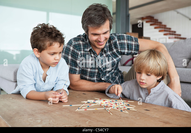 Boys playing pick up sticks with their father - Stock Image