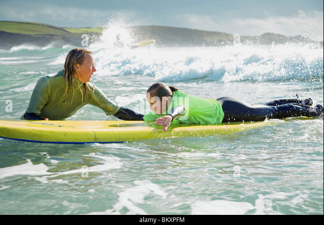 Woman in the sea holding a surfboard with a girl lying on it - Stock-Bilder