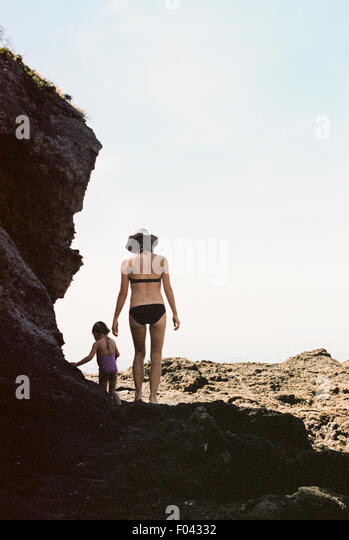Rear view of a woman wearing a bikini walking with her daughter across rocks by the ocean. - Stock Image
