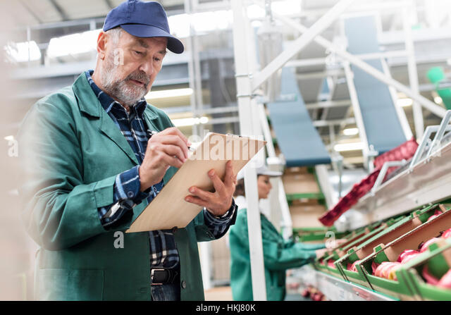 Manager with clipboard inspecting apples in food processing plant - Stock-Bilder