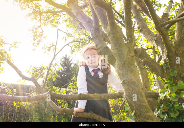 A little girl climbing a tree in her school uniform. - Stock Image