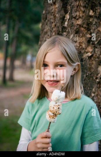 A young girl eating toasted marshmallow - Stock-Bilder