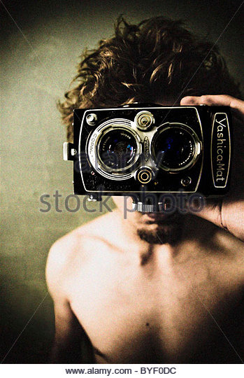 Young male holding a twin reflex camera in front of face - Stock Image
