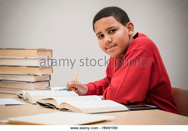 Smiling teenage boy studying with textbooks - Stock-Bilder