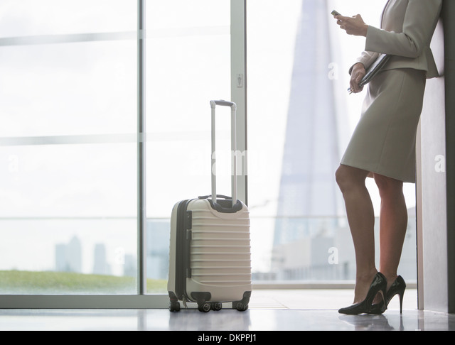Businesswoman with suitcase in airport - Stock Image