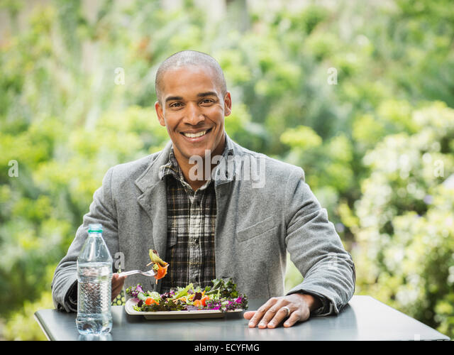 Black man eating lunch in urban park - Stock Image