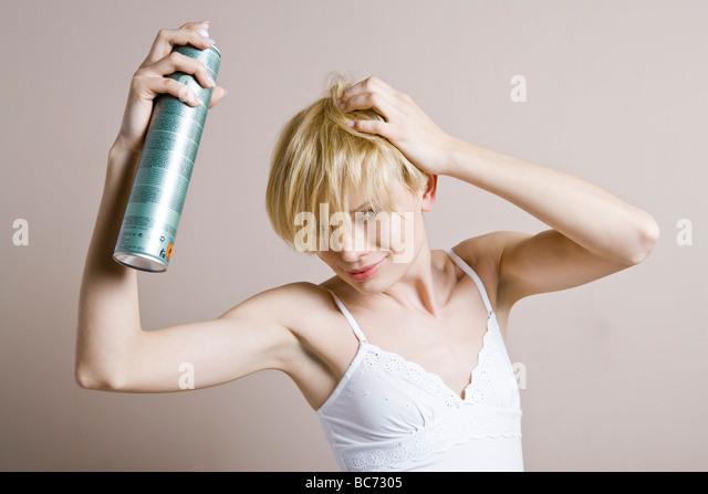 woman spraying hair - Stock Image