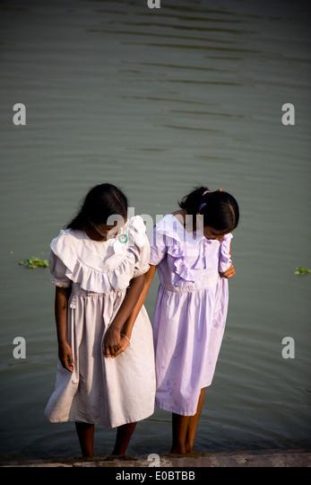 Indian school girls wash their feet beside a pond - Stock-Bilder