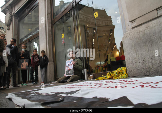 London, UK. 24th April 2014. A large banner seen between the two chained protesters outside The Benetton store on - Stock Image