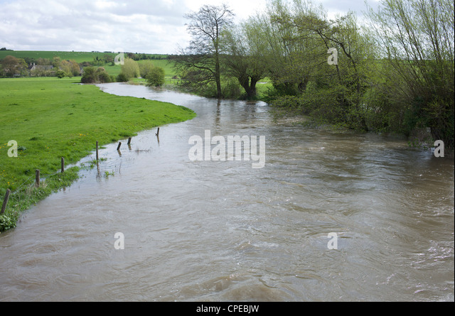 River Windrush in Oxfordshire beginning to overflow and burst its banks in April 2012 during a drought - Stock Image