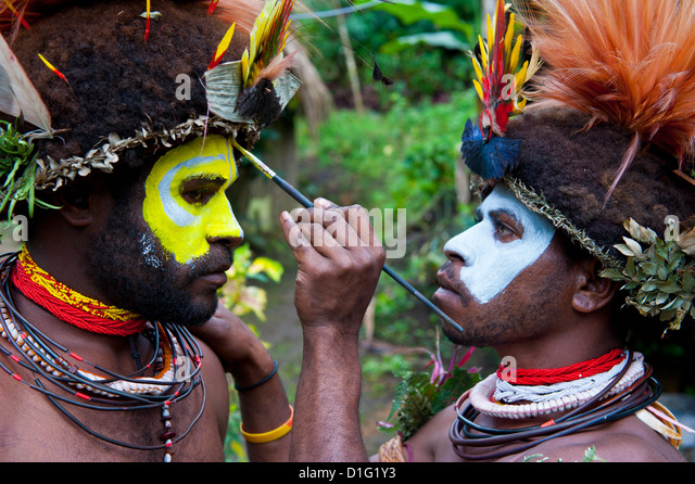 Tribesmen puting colour on their faces to celebrate the traditional Sing Sing in Paya in the Highlands, Papua New - Stock Image