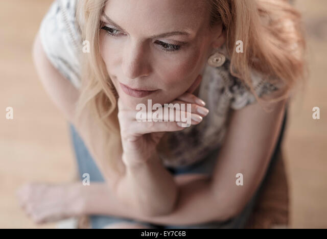 Mid-adult woman sitting on chair, thinking - Stock Image