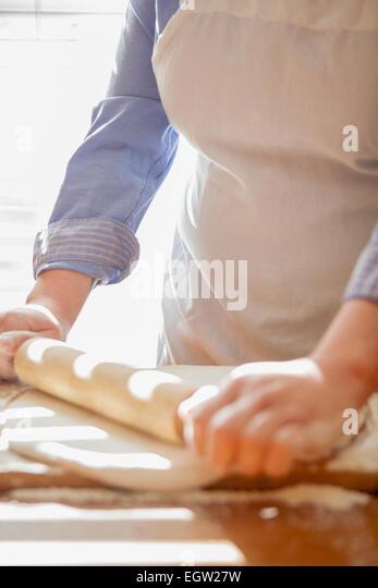 Woman rolling out dough. - Stock-Bilder