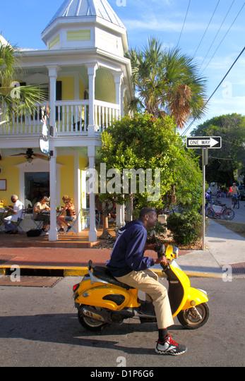 Florida Key West Florida Keys Bahamas Village Petronia Street Black man motor scooter La Creperie restaurant - Stock Image