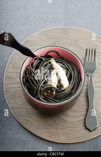 Black spaghetti with sardines and Espelette pepper - Stock-Bilder