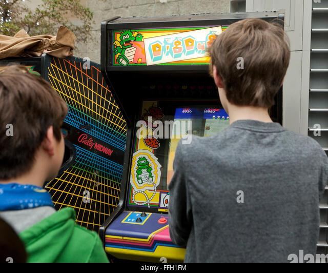 Young boys playing the classic Dig Dug video arcade game - USA - Stock Image